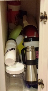 """My well-organized water bottle cabinet has become a plastic graveyard, full of old water pitchers and giant Country U.S.A. mugs. I am currently using a """"Sheriff"""" water bottle, which may or may not discourage pilfering."""